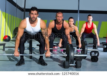 gym group with weight lifting bar workout in fitness exercise - stock photo