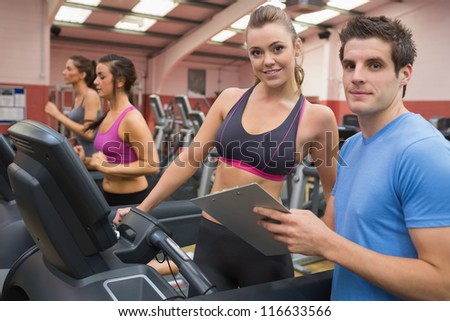 Gym Instructor and woman in the gym on the treadmill - stock photo