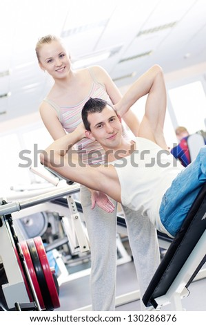 Gym man and woman doing exercise at the fitness club. Personal trainer.