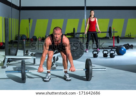 gym man and woman with weight lifting bar workout in crossfit exercise - stock photo
