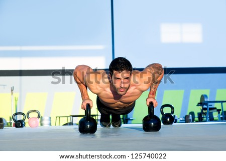 Gym man push-up strength pushup exercise with Kettlebell in a fitness workout - stock photo