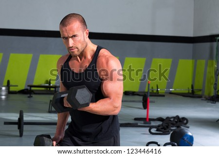 Gym man with dumbbells weights lifting exercise fitness workout - stock photo