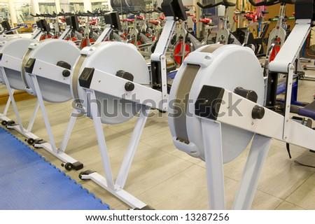 Gym or gymnasium equipment in a world-class facility suitable for athletes training for international events. Picture shows rowing machines. - stock photo