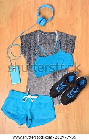 Gym outfit - workout clothing, running shoes, headphones and smartphone to listen to music while working out at the fitness center. Matching clothes, sports bra, shorts in blue and black. - stock photo