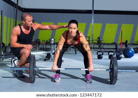 gym personal trainer man with weight lifting bar woman workout in fitness exercise - stock photo