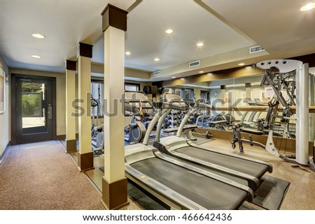 Gym room for residents in apartment building. Different exercise equipments and weights. Northwest, USA