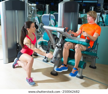 Gym seated leg curl machine exercise blond man and personal trainer woman - stock photo