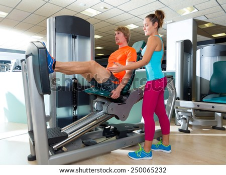Gym seated leg press machine blond man workout and personal trainer woman - stock photo