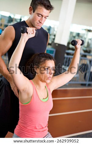 Gym: Trainer Assists Woman With Workout