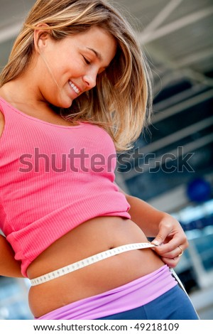 Gym woman measuring her waist - weight loss concepts - stock photo