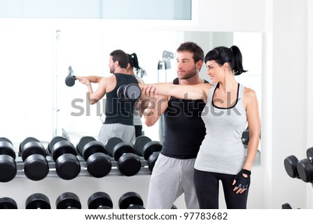 gym woman personal trainer man with weight training equipment - stock photo