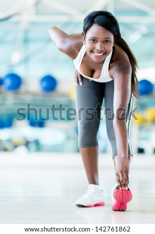 Gym woman stretching before her workout looking happy - stock photo