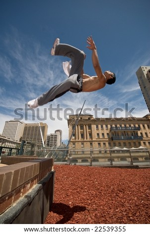 Gymnast (focus-movement) flips off wall - stock photo