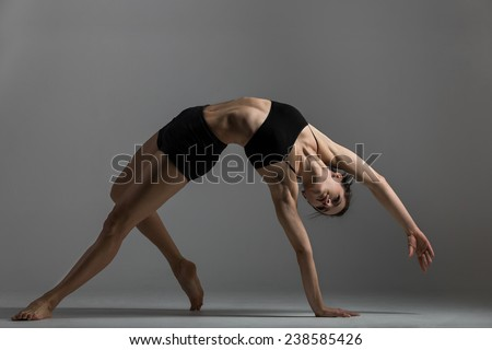 Gymnast girl is training performing exercise bridge, asana Camatkarasana, Wild Thing,  Dancing Dog yoga pose - stock photo