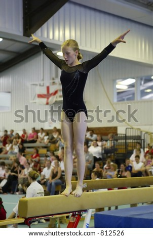 gymnast on beam during a competition - stock photo