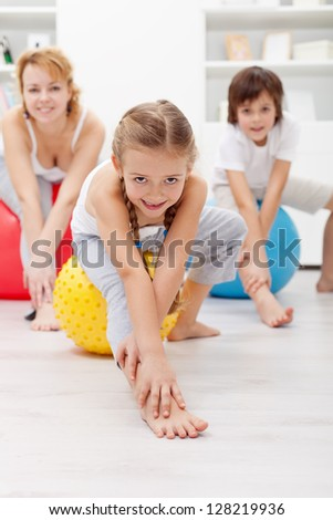 Gymnastic at home - woman and kids using large exercise balls