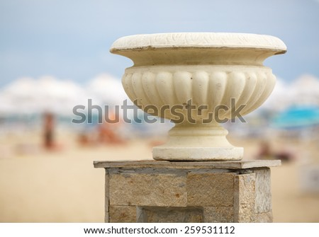 Gypsum vase in the old antique style on the street in bright sunny day. Shallow depth of field. - stock photo