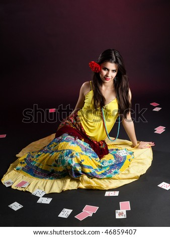 Gypsy woman sit with cards lay all around on the floor - stock photo