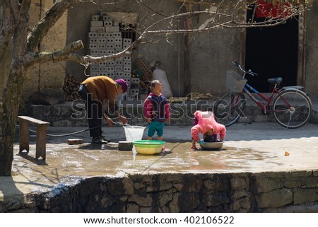 Ha Giang, Vietnam - Feb 14, 2016: Hmong grandmother help her children to wash their hair in front of the house in Dong Van district in sunny day