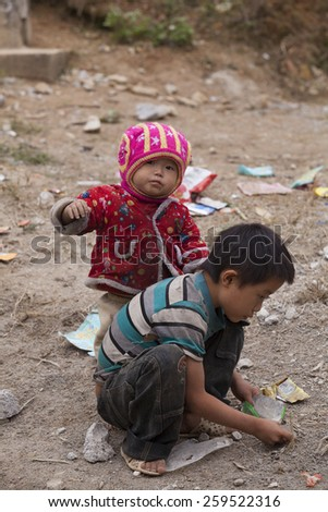 HA GIANG, VIETNAM - NOV 14, 2014: Close up photo of unidentified poor Hmong child eating candy on the dirty ground in Dong Van rocky plateau. Dong Van rocky plateau is a well known geopark.