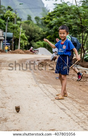 Ha Giang Vietnam - Septenber;18;2015:Hmong boy in Ha Giang Vietnam playing with his trowing top on the road during construction
