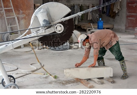 Ha Long Bay, Vietnam - April 17, 2015: Man cutting a block of white Marble in a Ha Long Bay  Ceramics factory. - stock photo