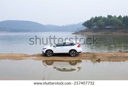 Ha Noi, Viet Nam - Dec 24, 2014: An SUV Honda model CRV 2014 crossing mud road in Vietnam - stock photo