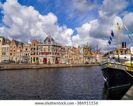 Haarlem, the Netherlands, June 10, 2011: View of the river Spaarne with the weighing house, Teylers museum and beautiful historic buildings and a boat on the quay under a beautiful sky