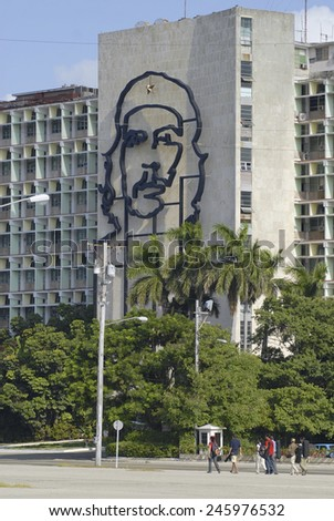 HABANA, CUBA - OCTOBER 21, 2006: Unidentified people pass iconic Ministry of Interior Defense building with the portrait of Che Guevara on it's facade on October 21, 2006 in Havana, Cuba. - stock photo
