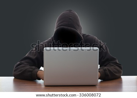 hacker and laptop on gray background - stock photo