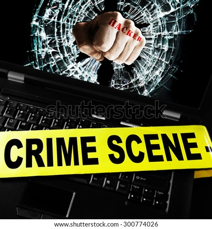 Hacker fist on laptop screen with crime scene tape  - stock photo