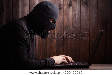 Hacker in a balaclava standing in the darkness furtively stealing data off a laptop computer on wooden background - stock photo