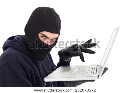 Hacker in balaclava standing and typing on laptop on white background - stock photo