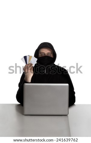 Hacker in black dress with credit cards on a silver laptop computer isolated on white background - stock photo