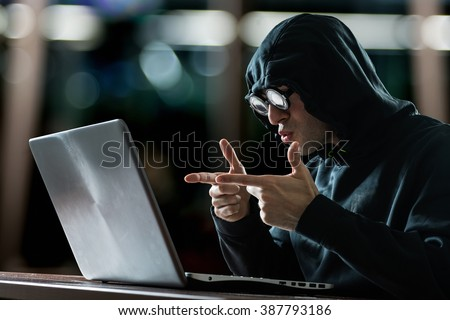 Hacker in front of his computer - stock photo