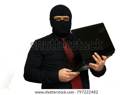 Hacker in the balaclava. In the hands of a laptop. computer crime