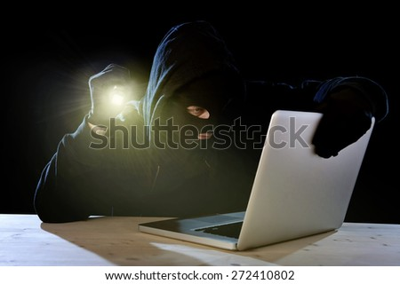 hacker man in black hood mask with computer laptop holding flashlight  in dangerous dark look hacking system having access to data info and privacy in business digital crack and cyber crime concept - stock photo