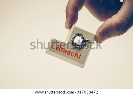 hacker's hand holding computer enter button with a hole and a message saying breach - computer security breach concept - stock photo