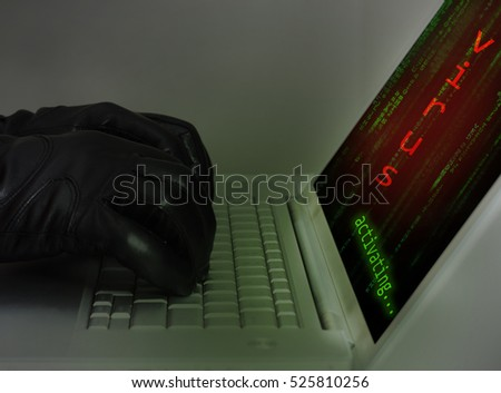Hacker wearing black gloves using a laptop injecting a virus