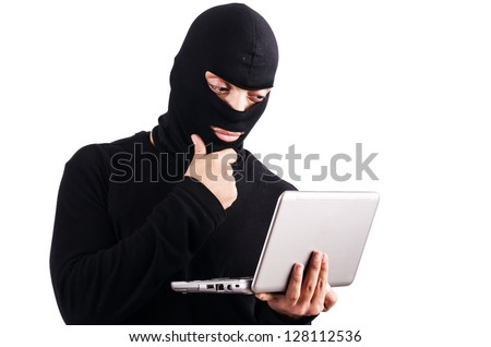 Hacker with computer wearing balaclava - stock photo