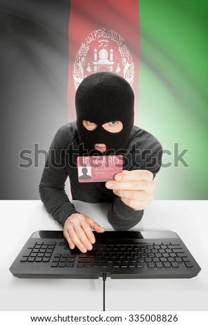 Hacker with ID card in hand and flag on background - Afghanistan - stock photo