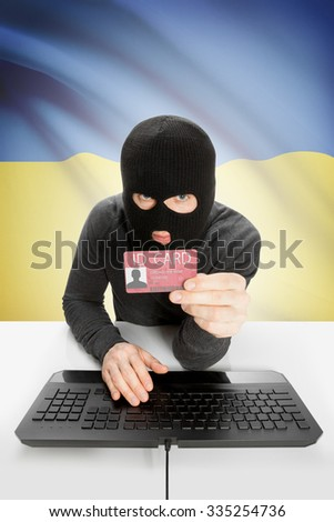 Hacker with ID card in hand and flag on background - Ukraine - stock photo