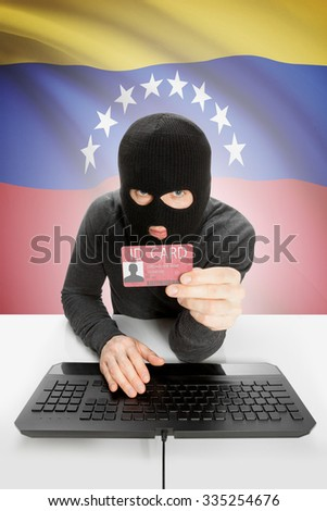 Hacker with ID card in hand and flag on background - Venezuela - stock photo