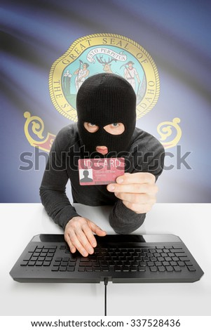 Hacker with ID card in hand and USA states flag on background - Idaho - stock photo