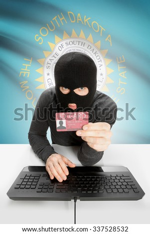 Hacker with ID card in hand and USA states flag on background - South Dakota - stock photo