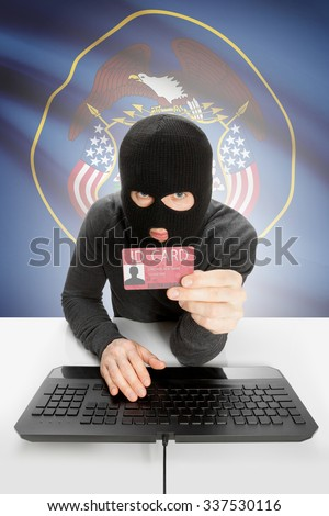 Hacker with ID card in hand and USA states flag on background - Utah - stock photo