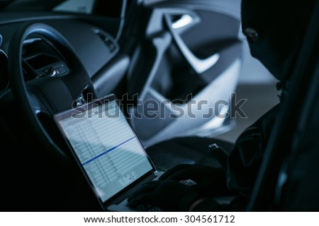 Hacker with Laptop in a Car at Night. Hacking WiFi Networks From Remote Location. - stock photo