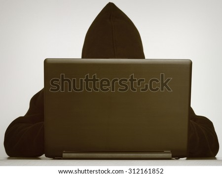 Hacker writing on a laptop and data safety - stock photo