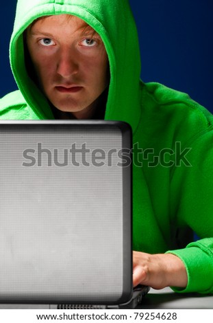 hacker. Young man with laptop is looking at camera - stock photo