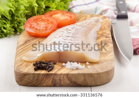 haddock fillet with tomato, pepper and coarse salt on a wooden board - stock photo